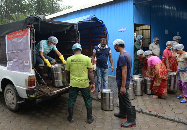 In this photograph taken on June 26, 2015, Akshaya Patra Foundation workers load metal containers with cooked meals for delivery to Nepal earthquake victims from a kitchen in Bhaktapur on the outskirts of Kathmandu. For thousands of quake victims in the Kathmandu valley, the arrival of a white van outside their tents twice a day provides rare comfort, holding the promise of a hot meal. Photo: AFP