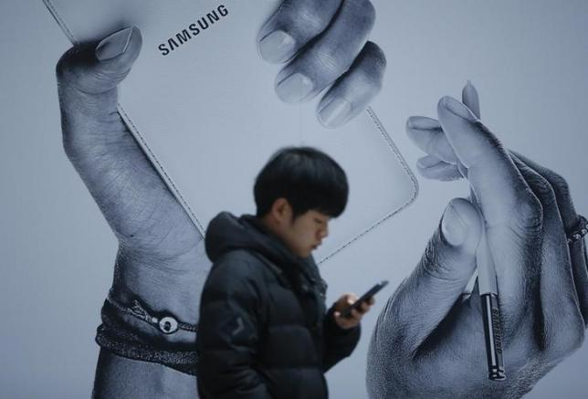 A passenger using his mobile phone walks past an advertisement promoting Samsung Electronics' Galaxy Note 3 at its exhibition hall at a railway station in Seoul November 25, 2013. REUTERS/Kim Hong-Ji/Files