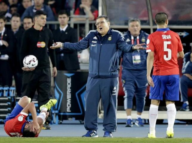 Argentina's coach Gerardo Martino react as as Chile's Mauricio Isla lies on the pitch and Chile's Francisco Silva looks on during their Copa America 2015 final soccer match at the National Stadium in Santiago, Chile, July 4, 2015. REUTERS/Jorge Adorno