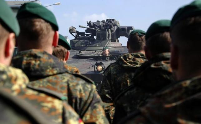 A Marder armoured infantry vehicle drives past German Bundeswehr armed forces soldiers of the 371st armoured infantry battalion during a media day of the NATO drill 'NOBLE JUMP 2015' at the barracks in Marienberg April 10, 2015.  REUTERS/Fabrizio Bensch