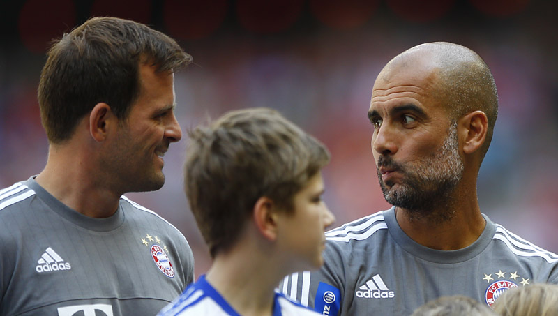Bayern's head coach Pep Guardiola from Spain, right, talks to goalkeeper coach Toni Tapalovic  during a show training after the team presentation for the upcoming German first division Bundesliga soccer season at the Allianz Arena in Munich, Germany, on Saturday, July 11, 2015. Photo: AP
