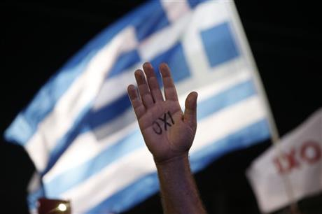 A demonstrator rises his hand reading the word ''No'' as a Greek flag waves during a rally organized by supporters of the No vote in Athens, Friday, July 3, 2015.  Photo: AP