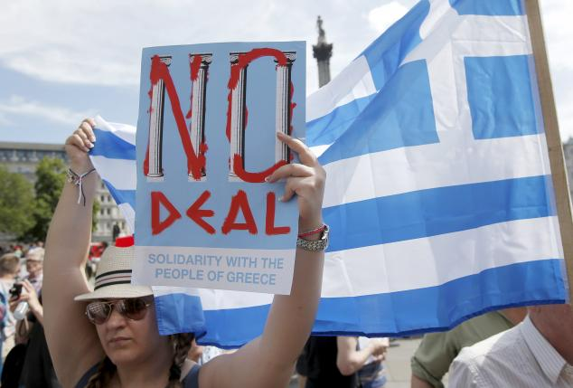 A woman holds the flag of Greece and a poster in favour of the 'NO' campaign, at the 'Greek solidarity festival' in Trafalgar Square, London, Britain, July 4, 2015. REUTERS/Peter Nicholls