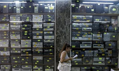 A woman reads a paper in front of a shop selling old stereo systems in Athens, Tuesday, July 21, 2015. Banks reopened Monday for the first time in three weeks. But for most Greeks, already buffeted by six years of recession, Monday was all about rising prices as tax hikes demanded by creditors took effect.  AP