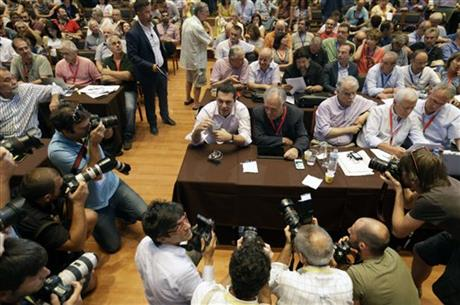 Greek Prime Minister Alexis Tsipras holds a bottle of water as he is surrounded by photographers during a meeting of ruling radical left Syriza party's central committee in Athens, on Thursday, July 30, 2015. AP
