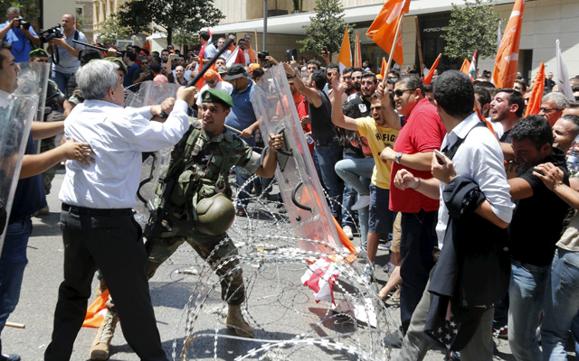 Lebanese Parliament member Hikmat Deeb tries to stop a Lebanese army soldier during a scuffle with members of the Free Patriotic Movement, who were blocked by the army, as they proceeded towards the government npalace in Beirut, on Thursday. Photo: Reuters