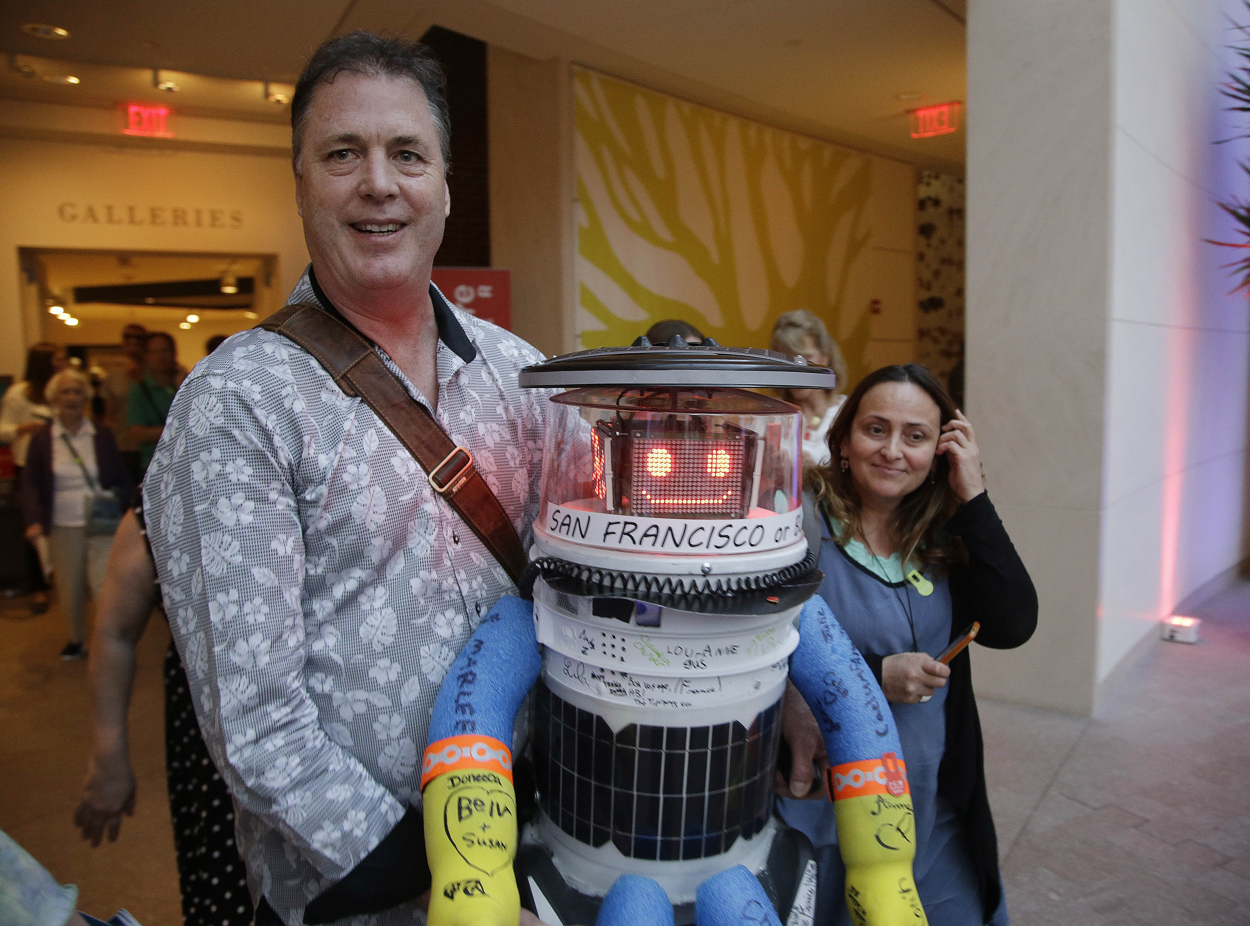 Co-creator David Harris Smith carries hitchBOT, a hitchhiking robot, during its' introduced to an American audience at the Peabody Essex Museum Thursday, July 16, 2015, in Salem, Mass. HitchBOT is set to embark on its' first cross-country hitchhiking trip of the U.S., after completing similar tips in Canada and Europe. The plans are for hitchBot to leave the Boston area Friday with a final destination goal of reaching San Francisco. Photo: AP