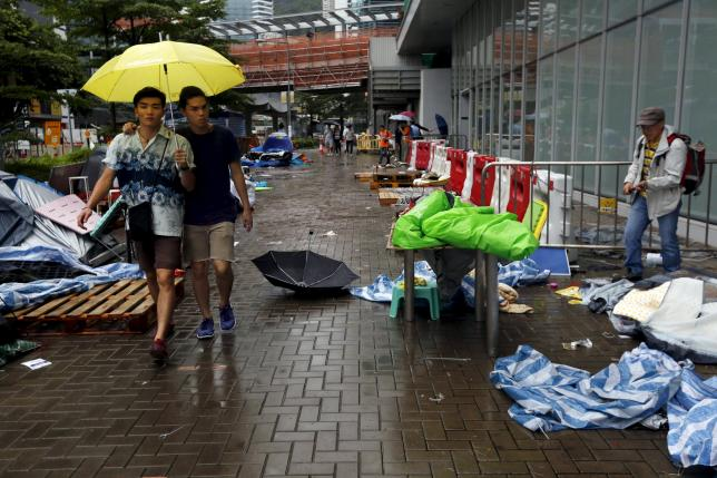 One of the remaining pro-democracy protester (R) packs his belongings as two others carrying a yellow umbrella, the symbol of the Occupy Central movement, walk past outside the government headquarters in Hong Kong, China June 24, 2015. REUTERS/Bobby Yip
