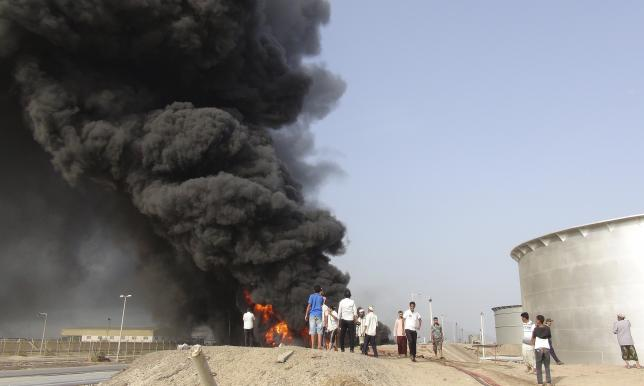People gather at the site of a fire caused by missiles fired by Houthi fighters at storage tanks of the oil refinery in Yemen's southern port city of Aden June 27, 2015.  REUTERS/Stringer