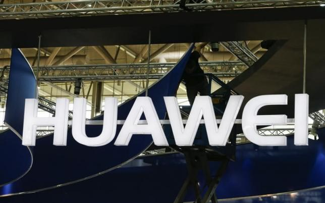 A worker adjusts the logo at the stand of Huawei at the CeBIT trade fair in Hanover March 15, 2015. Photo: Reuters