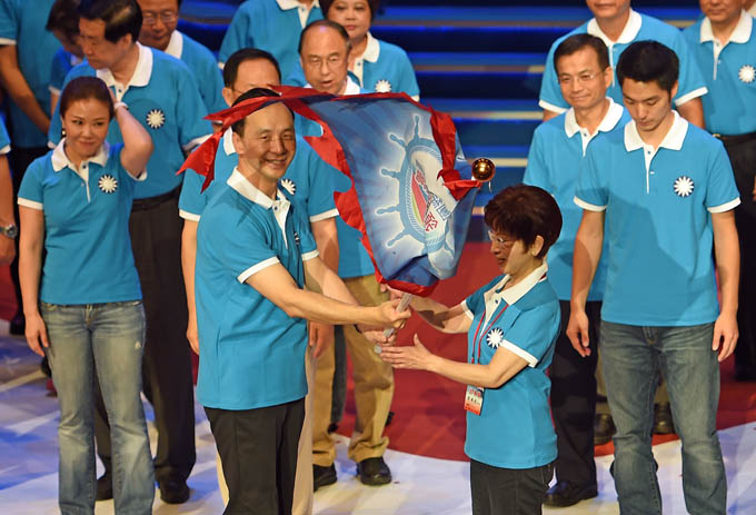 Hung Hsiu-chu (R), the ruling Kuomintang (KMT) presidential Candidate, receives the party flag from Eric Chu, Chairman of the KMT during the KMT's party congress in Taipei on July 19, 2015.  Taiwan's ruling Kuomintang (KMT) officially endorsed wildcard candidate Hung Hsiu-chu to run for president next year, as the deeply divided party faces a battle to regain public support. Photo: AFP