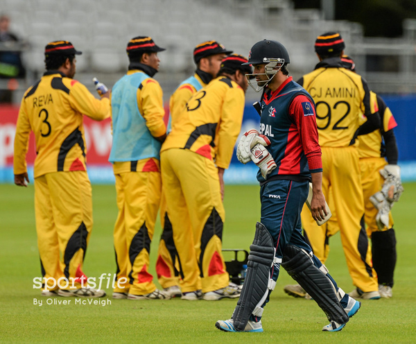 Nepalu0092s Binod Bhandari walks back to the pavilion as Papua New Guinea players celebrate during their ICC World Twenty20 Qualifiers Group A match in Dublin, Ireland on Friday. Photo: ICC / SPORTSFILE