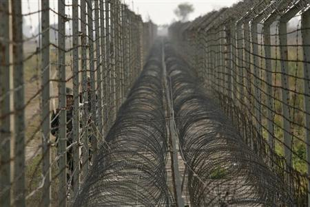 Indian Border Security Force (BSF) soldiers patrol the fenced border with Pakistan in Suchetgarh, southwest of Jammu January 16, 2013. REUTERS/Mukesh Gupta/Files