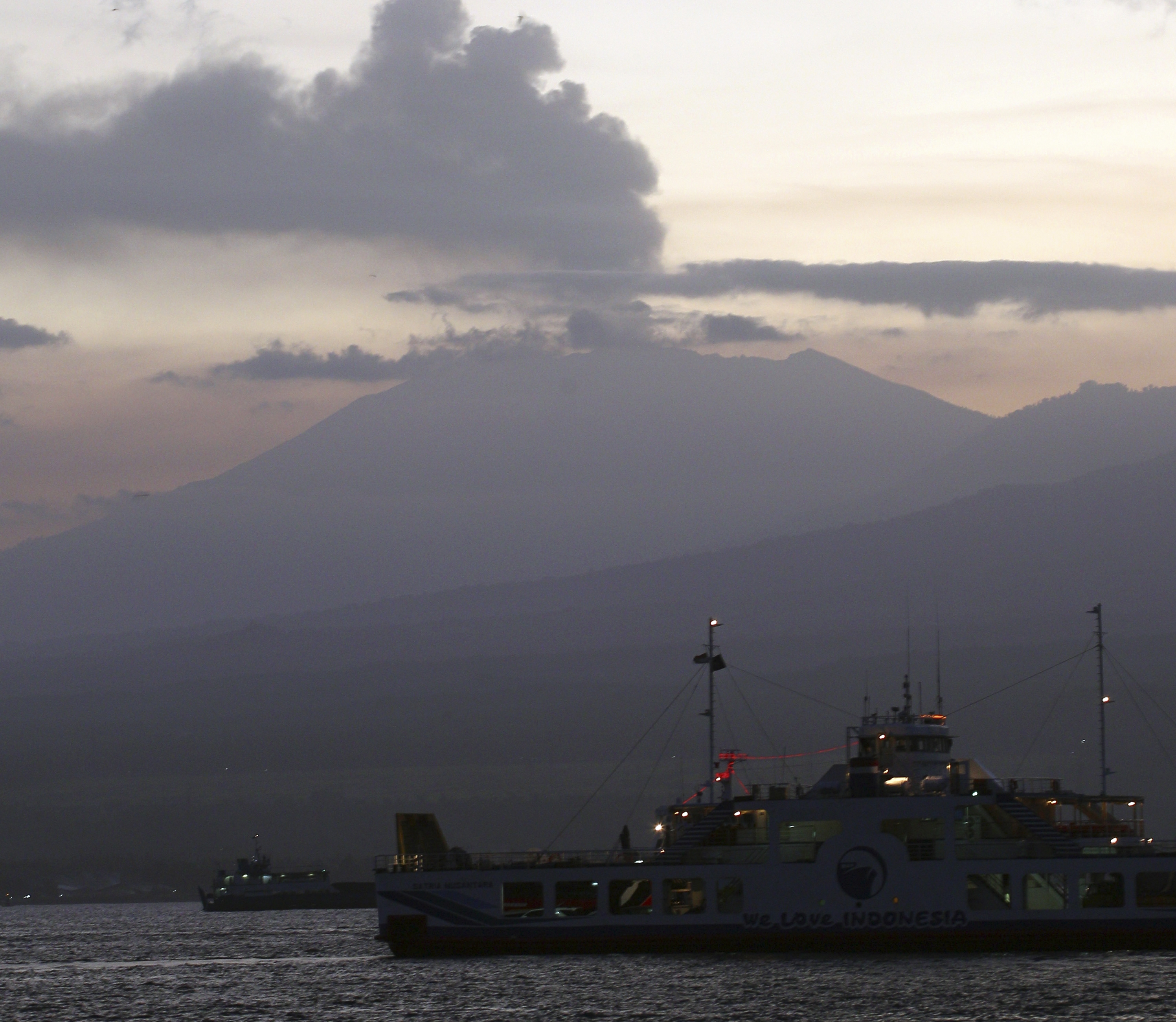 A ferry boat crosses the Bali Strait to carry Indonesians to Ketapang port, East Java, from Gilimanuk port, West Bali, Indonesia as Mount Raung spews volcanic smoke, Sunday, July 12, 2015. Ash spewing from the volcano sparked chaos for holidaymakers as airports closed and international airlines canceled flights to tourist hotspot Bali, stranding thousands. Photo: AP