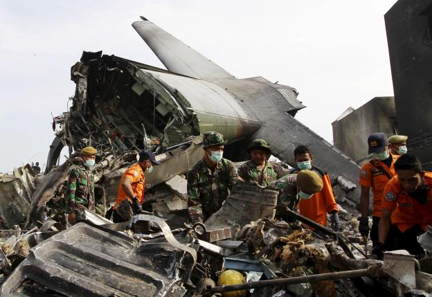 Indonesian soldiers and search and rescue teams  remove debris from the crash site of a military C-130  transport plane which went down yesterday in a residential area of Medan, North Sumatra,  Indonesia,  July 1, 2015. REUTERS/Roni Bintang