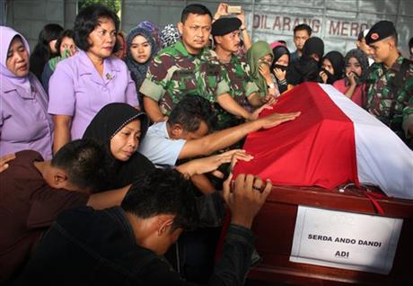 Relatives of Sgt. Ando Dandi, one of the victims of a military plane that crashed onto a residential area on Tuesday, pray at his coffin at Suwondo Airbase in Medan, North Sumatra, Indonesia, Wednesday, July 1, 2015. The C-130 Hercules crashed shortly after takeoff in the country's third largest city on June 30. AP