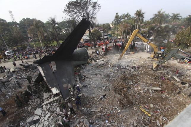 Security forces use heavy equipment to remove debris at the crash site of an Indonesian military C-130 transport plane which crashed yesterday into a residential area in Medan, North Sumatra, Indonesia July 1, 2015 in this photo taken by Antara Foto.      REUTERS/Septianda Perdana/Antara Foto