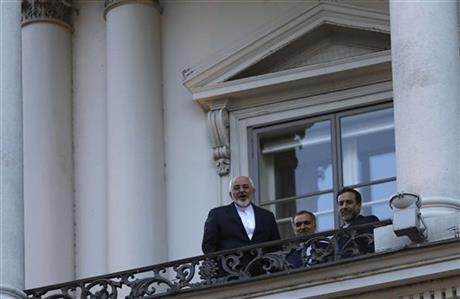 Iranian Foreign Minister Mohammad Javad Zarif, left, talks to journalist from a balcony of the Palais Coburg hotel where the Iran nuclear talks are being held in Vienna, Austria, Thursday, July 9, 2015. AP