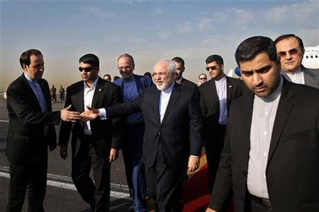 Iran's Foreign Minister Mohammad Javad Zarif, who is also Iran's top nuclear negotiator, center, shakes hands with an official upon arrival at the Mehrabad airport in Tehran, Iran, Wednesday, July 15, 2015. AP