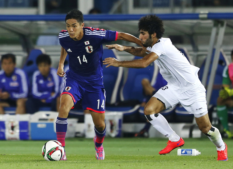 Japan's Yoshinori Muto (L) and Iraq's Sameh Saeed Mejbel fight for the ball during their international friendly soccer match in Yokohama, south of Tokyo, June 11, 2015. Photo: Reuters