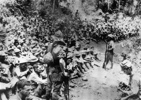 FILE - In this 1942 file photo provided by U.S. Marine Corps, Japanese soldiers stand guard over American war prisoners just before the start of the Bataan Death March following the Japanese occupation of the Philippines. AP