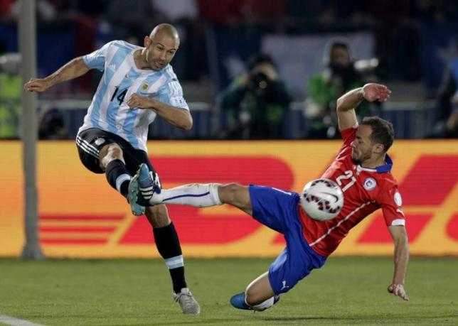 Argentina's Javier Mascherano (L) kicks the ball next to Chile's Marcelo Diaz during their Copa America 2015 final soccer match at the National Stadium in Santiago, Chile, July 4, 2015. REUTERS/Jorge Adorno