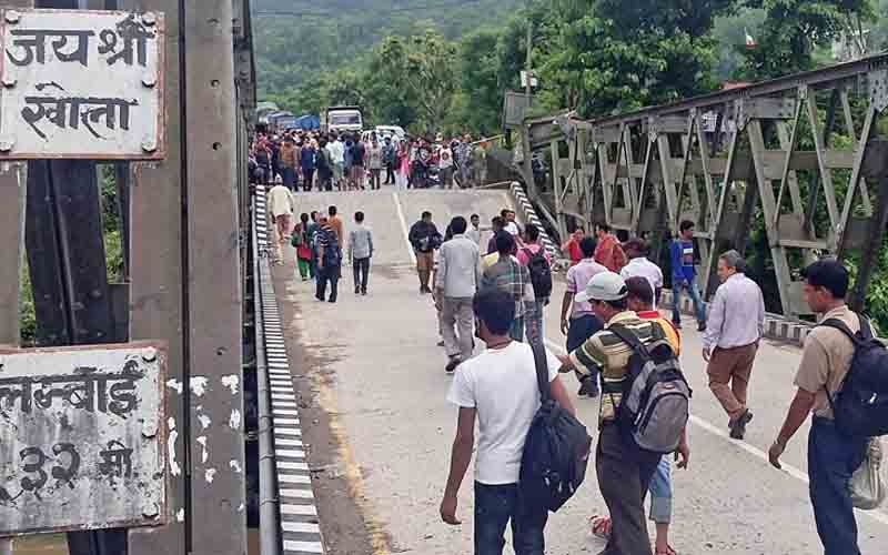 People walking over Jayashree Bridge that collapsed at Gaindakot of Nawalparasi, on Tuesday.