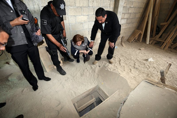 Mexicou0092s Attorney General Arely Gomez Gonzalez (second from right) looks into the entrance of a tunnel connected to the Altiplano Federal Penitentiary and used by drug lord Joaquin nu0091El Chapou0092 Guzman to escape, in Almoloya de Juarez, on the outskirts of Mexico City, on Sunday. Photo: Reuters