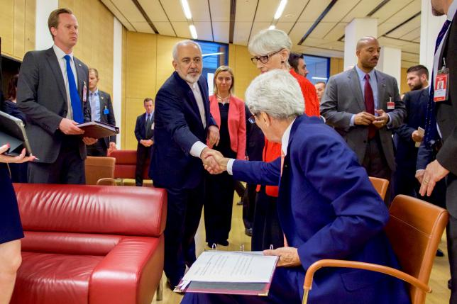 U.S. Secretary of State John Kerry (seated) shakes hands with Iranian Foreign Minister Javad Zarif as he prepares to leave the Austria Center in Vienna, Austria, July 14, 2015.  REUTERS/US State Department/Handout via Reuters