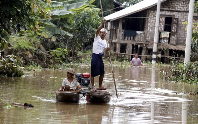 Residents riding a boat in a flooded area as they transport aid for their village at Kawlin township, Sagaing division, Myanmar, on Thursday. Heavy rains caused flooding in over 20,000 acres of rice field and in about a hundred villages, killing at least eight people. Photo: Reuters