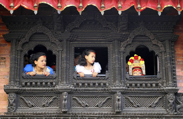 Sambeg Shakya, 6, observes the Indra Jatra Festival from a window of a house of the Living Goddess Kumari in Kathmandu September 16, 2011. Sambeg Shakya was hailed last year by Buddhist priests as Ganesh, or the god of good fortune, since when he has led several processions of Nepal's better-known 'living goddesses', also known as Kumari. The centuries-old ritual, once used by now-toppled kings who thought it would make them stronger, was the climax of the annual Hindu festival of Dasain, which lasts for two weeks and has become a major tourist attraction in Nepal.  Sambeg will continue in his supporting role until he is big enough to fit in a chariot pulled by men, after which he must return to real life. Picture taken September 16, 2011. Photo: Reuters