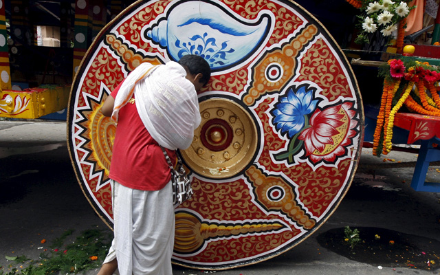 A Hindu devotee seeks blessings from the  chariot of Lord Jagannath, during the annual Rath Yatra, in Kolkata on Saturday. Photo Reuters