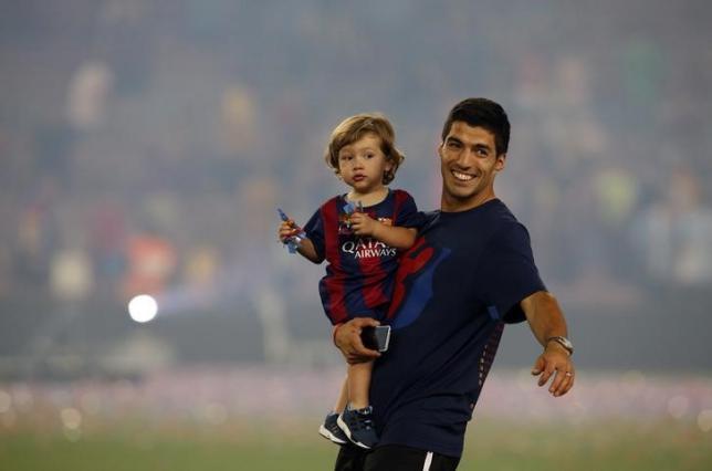 Barcelona's Luis Suarez holds his son Benjamin after the celebration parade at Camp Nou stadium in Barcelona, Spain, June 7, 2015. REUTERS/Albert Gea/Files