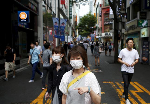 Women wearing masks to prevent contracting Middle East Respiratory Syndrome (MERS) walk at Myeongdong shopping district in central Seoul, South Korea, July 9, 2015. Photo: Reuters