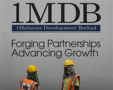 In this May 14, 2015 photo, construction workers chat in front of a billboard for state investment fund 1 Malaysia Development Berhad (1MDB) at the fund's flagship Tun Razak Exchange development in Kuala Lumpur, Malaysia. AP