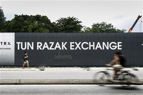 In this May 14, 2015 photo, Malaysians pass by a billboard for the Tun Razak Exchange, a development by state investment fund 1 Malaysia Development Berhad (1MDB) in Kuala Lumpur, Malaysia. Malaysia's state investment fund 1MDB says it has never provided any funds to Prime Minister Najib Razak, denying reports that entities linked to the fund had funneled $700 million ($2.6 billion) into Najib's personal accounts. AP