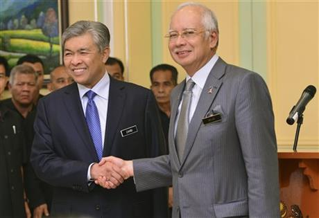 Malaysia's Prime Minister Najib Razak, right, shakes hands with his newly-appointed Deputy Prime Minister Ahmad Zahid Hamidi after addressing a press conference at the prime minister's office in Putrajaya, Malaysia, Tuesday, July, 28, 2015.  AP