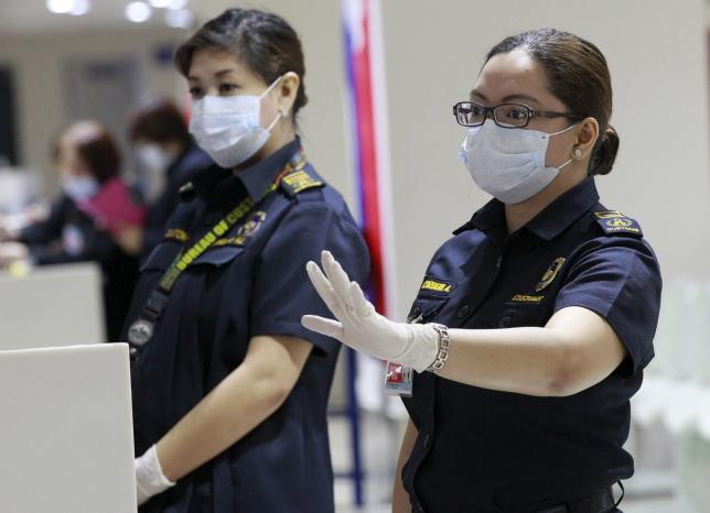 File- A customs inspector wearing a face mask gestures as she waits for flight passengers arriving from South Korea at the arrival area of Ninoy Aquino International Airport in Manila, June 9, 2015. Photo: Reuters