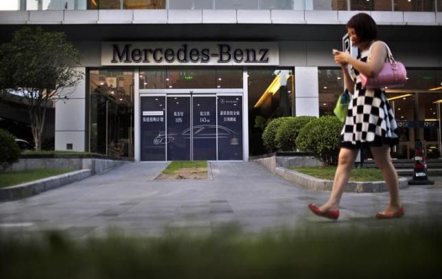A woman walks past a Mercedez-Benz car dealership in downtown Shanghai August 5, 2014. REUTERS/Carlos Barria/Files
