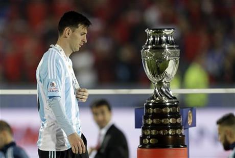 Argentina's Lionel Messi walks by the Copa America trophy after receiving the silver medal after the final game with Chile at the National Stadium in Santiago, Chile, Saturday, July 4, 2015. AP