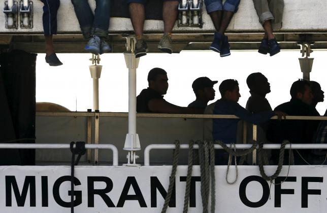 Migrants wait to disembark from the Migrant Offshore Aid Station (MOAS) ship MV Phoenix in the Sicilian harbour of Messina, Italy July 15, 2015. REUTERS/Antonio Parrinello   TPX IMAGES OF THE DAY