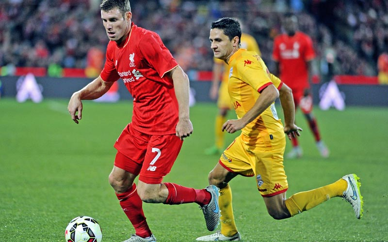 Liverpool's James Milner and Adelaide's Marcelo Carrusca vie for the ball during their friendly match in Adelaide on Monday. Photo: AFP