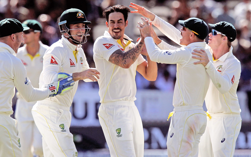 Australia's Mitchell Johnson (centre) celebrates with his teammates after taking the wicket of England's Jos Buttler on the fourth day of their second Ashes Test match at Lord's cricket grounds in London on Sunday. Photo: AFP