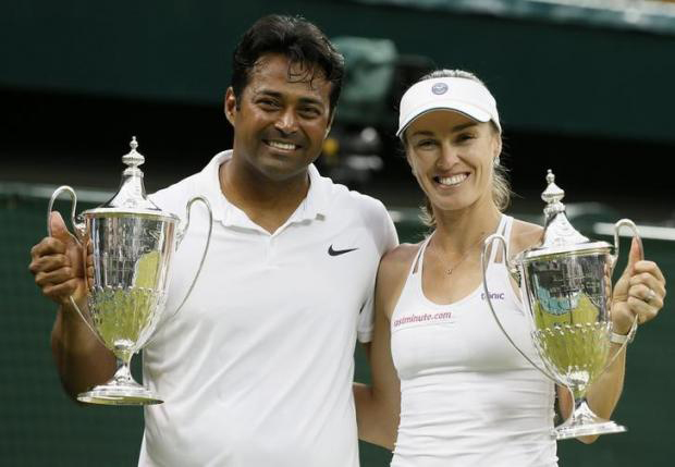 Leander Paes of India and Martina Hingis of Switzerland show off their trophies after winning their Mixed Doubles Final match against Timea Babos of Hungary and Alexander Peya of Austria at the Wimbledon Tennis Championships in London, July 12, 2015. nPhoto: Reuters/Stefan Wermuth