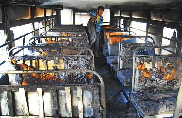 A driver removing the burnt parts of seats after party workers of Netra Bikram Chand-led CPN Maoist torched a bus of Modern Indian School in Kirtipur, Kathmandu, on Wednesday. Photo: Bal Krishna Thapa/THT