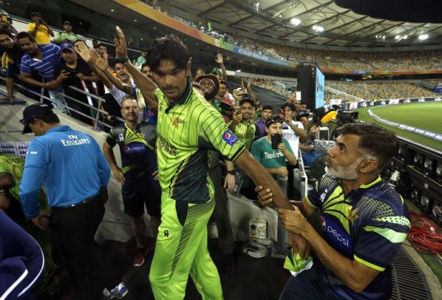 Pakistan's Mohammad Irfan (C) is pulled back by a team official after walking off the field having won the Cricket World Cup match against Zimbabwe at the Gabba in Brisbane March 1, 2015. REUTERS/Jason Reed
