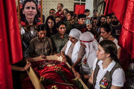 Mourners gather around the body of Gulay Ozarlan, a DHKP-C militant, that was killed in a gunfight with police during a major police sweep that was launched against the outlawed group as well as suspected members of  the outlawed Kurdish rebel group, the PKK and also Islamic State group militants, during her funeral In Istanbul, Saturday, July 25, 2015. Turkish media claimed Ozarlan was wanted by police on suspicion that she planned a suicide attack. (AP Photo/Cagdas Erdogan) TURKEY OUT