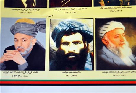 An Afghan shop clerk shows a calendar with pictures of Afghan leaders including Mullah Mohammad Omar, center, in Kandahar, south of Kabul, Afghanistan, Thursday, July 30, 2015. AP