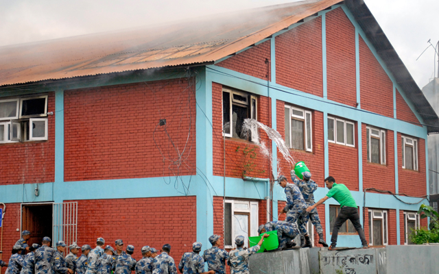 Members of the Armed Police Force ndousing the fire that engulfed a lab of Nepal Academy of Science and Technology in Khumaltar, Lalitpur, on Thursday. Photo: Naresh Shrestha/ THT