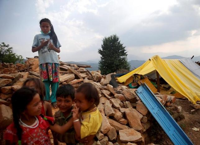 FILE: Children stand on the remains of houses which were destroyed by earthquakes in Sindhupalchok district, Nepal, May 13, 2015. Photo: Reuters